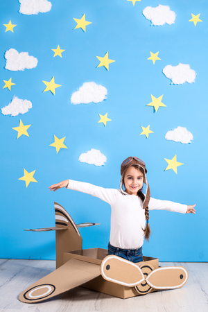 Little dreamer girl playing with a cardboard airplane at the studio with blue sky and white clouds background.