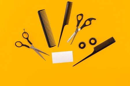 Hairdresser tools on yellow background with copy space, top view, flat lay. Stock Photo