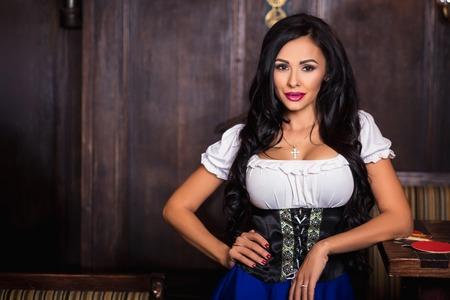 Oktoberfest woman wearing a traditional Bavarian dress dirndl posing at bar