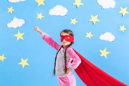 Little child plays superhero. Kid on the background of bright blue wall.