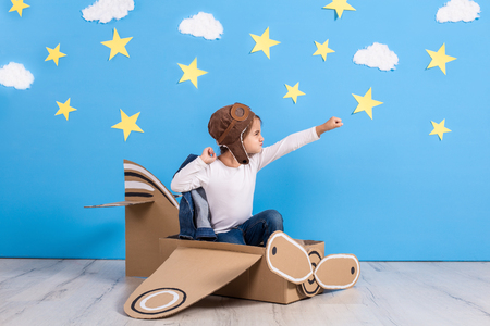 Little child girl in a pilots costume is playing and dreaming of flying over the clouds. Stockfoto