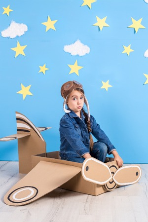 Little child girl in a pilots costume is playing and dreaming of flying over the clouds. 版權商用圖片