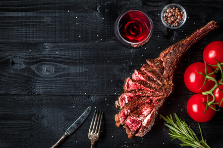 Barbecue dry aged rib of beef with spice, vegetables and glass of red wine close-up on black wooden background