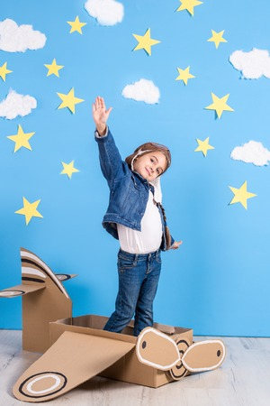 Little child girl in a pilots costume is playing and dreaming of flying over the clouds. Stock Photo