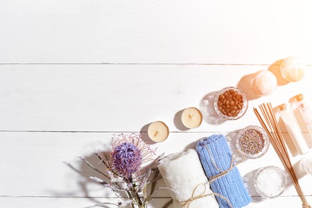 Spa products. Bath salts, dry flowers lavender, soap, candles and towel. Flat lay on white wooden background, top view. Sun flare Stock Photo