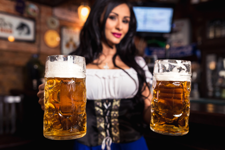 Young sexy Oktoberfest waitress, wearing a traditional Bavarian dress, serving big beer mugs at bar.