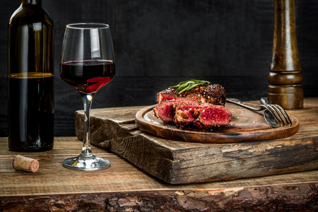 Grilled ribeye beef steak with red wine, herbs and spices on wooden table