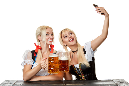 Young women in traditional Bavarian clothes, dirndl or tracht, on white background.