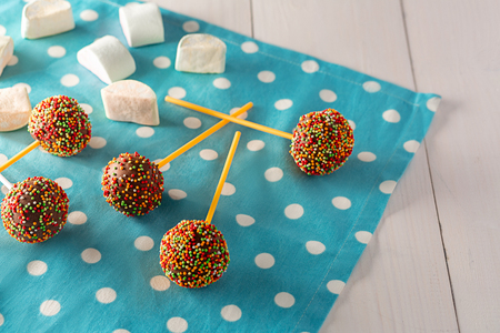 kids birthday party: Homemade tiny cakes - cakepops for childrens birthday on a white wooden background.