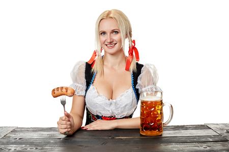 白い背景の上のビールでテーブルに座ってのギャザー スカートの若いババリア地方女性 写真素材
