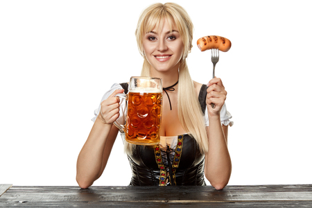 Young bavarian woman in dirndl sitting at table with beer on white background