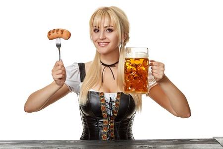 Junge bayerische Frau im Dirndl, der bei Tisch mit Bier auf weißem Hintergrund sitzt Standard-Bild - 87472186
