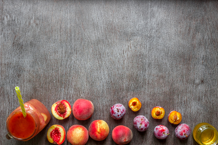 A glass of smoothies made of peach and plums on a wooden background. Top view. Copy space. Still life. Flat lay Stock Photo