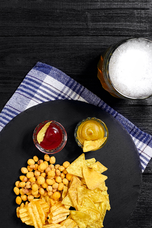 Overhead view of beer glass and snacks with sauce on black wooden table. Stock Photo