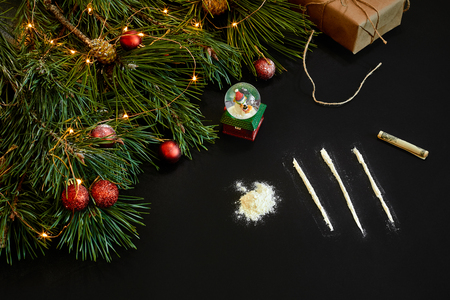 Cocaine divided into paths with Xmas toys and spruce branch on black background top view. Stock Photo