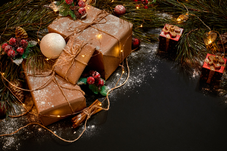 Christmas gifts and garland near green spruce branch on a black background. Christmas background. Top view.