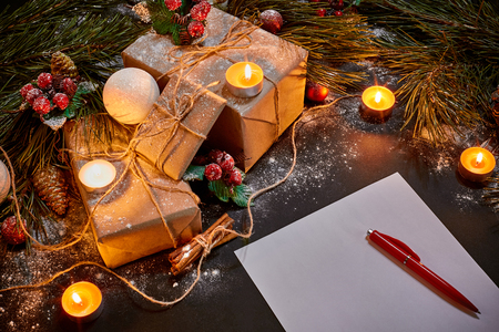 tinsel: Christmas gifts, burning candles and notebook lying near green spruce branch on black background top view. Space for text