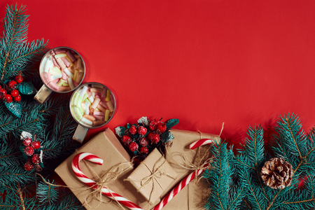 Fir branch, gift box and two cups of cocoa with marshmallows on red background
