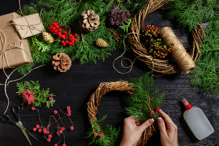 Top view of female hands make a Christmas wreath. Packed gifts and scrolls, spruce branches and tools on wooden table. Stock Photo