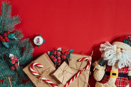 Fir branch, gift box and toy Santa on red background