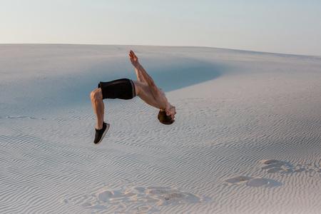 L'homme étudie le parkour seul. Acrobaties dans le sable