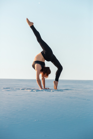 inversion: Young woman practicing inversion balancing yoga pose handstand on sand. Stock Photo