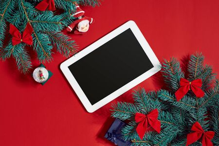 christmas decorations and white tablet with black screen on hot red background christmas and new