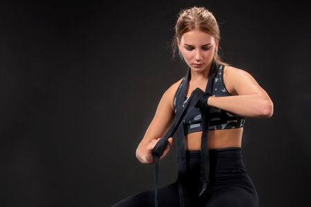 venganza: Young fit woman wrapping her arms with bandage tape. Attractive girl preparing for the kickboxing training.