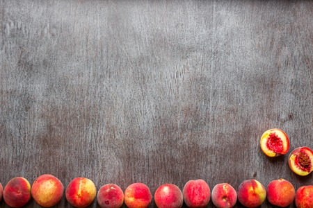 Fresh peaches fruits on dark wooden rustic background, top view