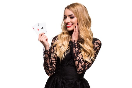 Beautiful young woman holding two ace of cards in her hand isolated on black background