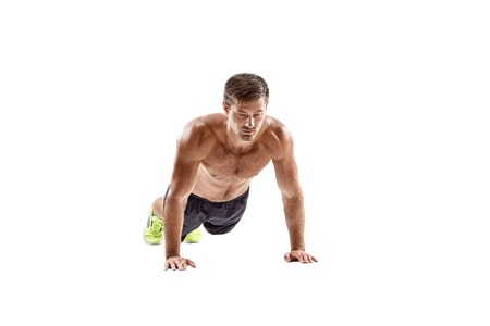 Push up fitness man doing push-up bodyweight exercise on gym floor. Athlete working out chest muscles strength training indoors