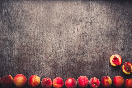Fresh peaches fruits on dark wooden rustic background, top view. Toned Stock Photo