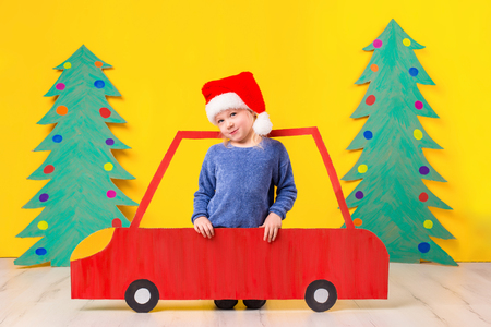 Child with Christmas hat driving a car made of cardboard. Christmas concept. New Years holidays. Stock Photo