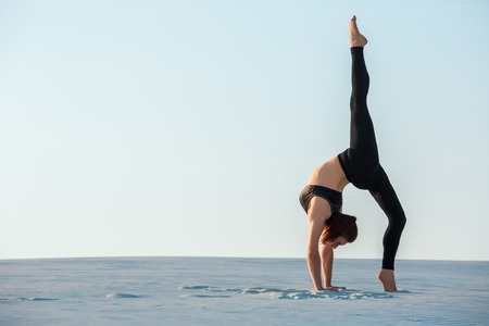 Young woman practicing inversion balancing yoga pose handstand on sand. Imagens