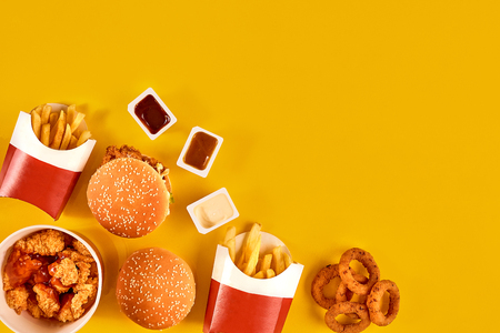 Fast food dish top view. Meat burger, potato chips and wedges. Take away composition. French fries, hamburger, mayonnaise and ketchup sauces on yellow background. Stock Photo