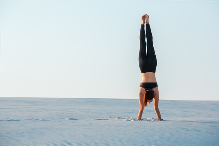Young woman practicing inversion balancing yoga pose handstand on sand. Sunset and white sand.