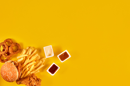 Fast food dish top view. Meat burger, potato chips and wedges. Take away composition. French fries, hamburger, mayonnaise and ketchup sauces on yellow background. Reklamní fotografie