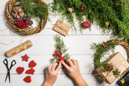 Weihnachtshandgemachter diy Hintergrund. Basteln Weihnachtskranz und Ornamente. Draufsicht des weißen Holztischs mit den weiblichen Händen.