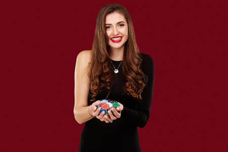 Casino, gambling, poker, people and entertainment concept - woman poker player in black dress with chips in hands on red background.