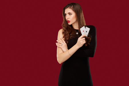 Beautiful caucasian woman in black dress with poker cards gambling in casino