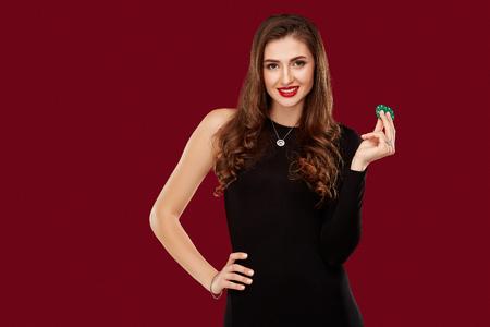 La donna abbastanza lunga dei capelli in vestito nero tiene i chip per il gioco