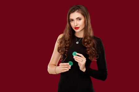 Pretty long hair woman in black dress holding chips for gambling Foto de archivo