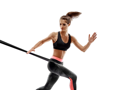 Woman exercising fitness resistance bands in studio silhouette isolated on white background Stock Photo