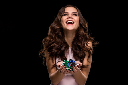 Il giocatore di poker femminile con le unghie nere di vernice tiene le sue fiches da poker per fare una scommessa. Concetto di gioco d'azzardo e casinò