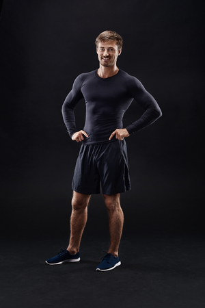 Male model in active sportswear against black background with copy space