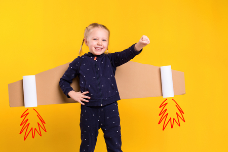 A little child girl is wearing homemade cardboard flying wings, pretending to be a pilot for a craft, imagination or exploration concept. Stock Photo