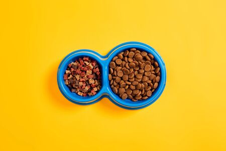 Dry pet food in bowl on yellow background top view