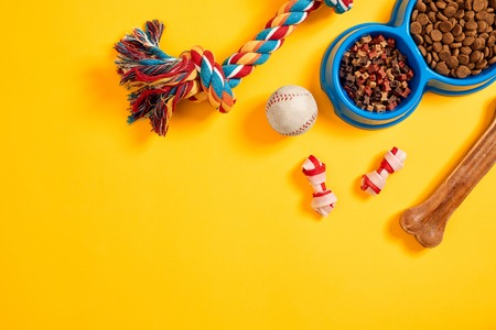 Toys -multi coloured rope, ball and dry food. Accessories for play on yellow background top view