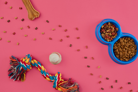 Toys -multi coloured rope, ball, dry food and bone. Accessories for play on pink background top view