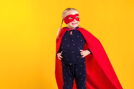 Funny little power superhero child girl in a red raincoat and a mask. Superhero concept. Standard-Bild